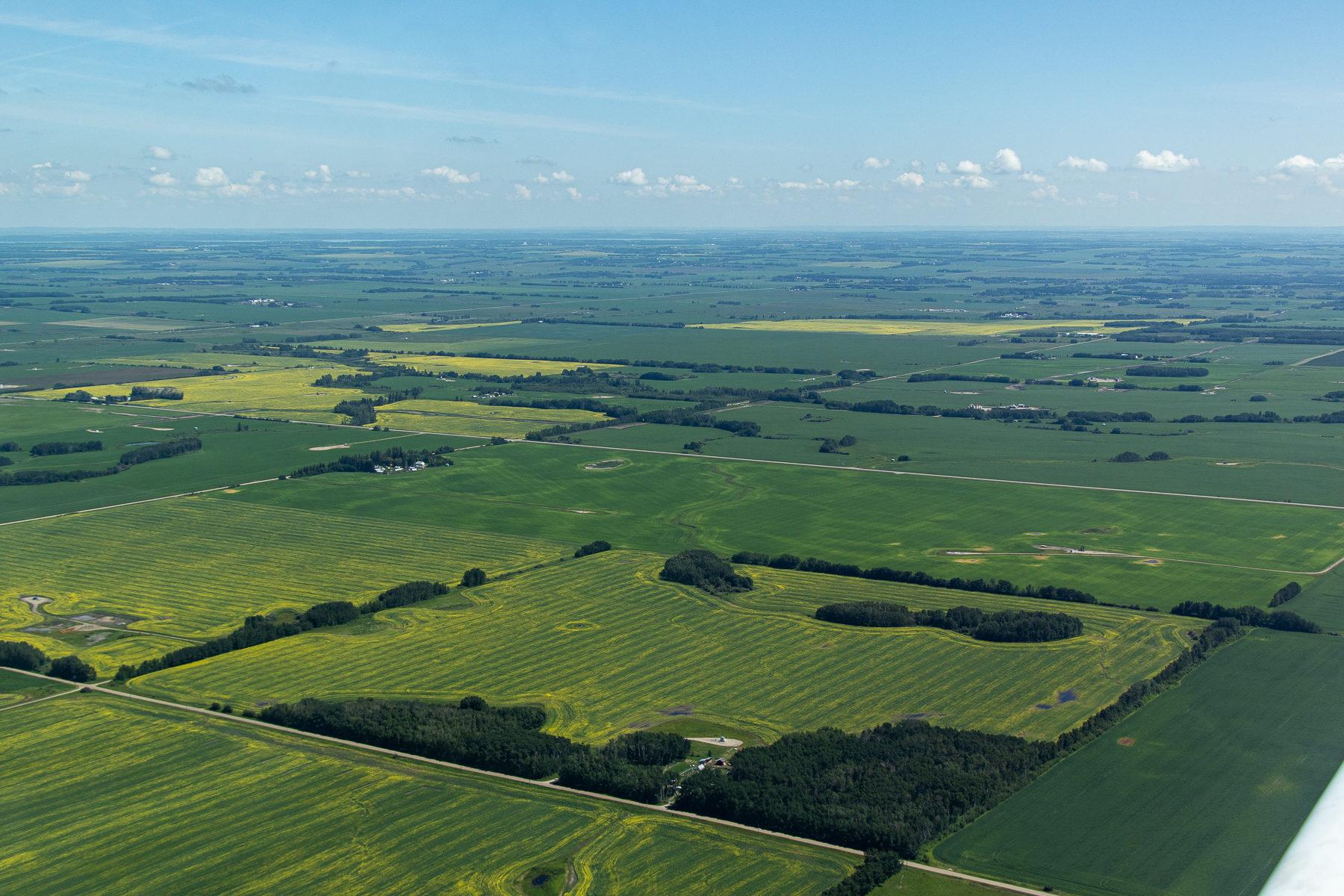 Von oben sieht Alberta ganz klein aus. In der Ferne sind die Rocky Mountains von Wolken verhangen.