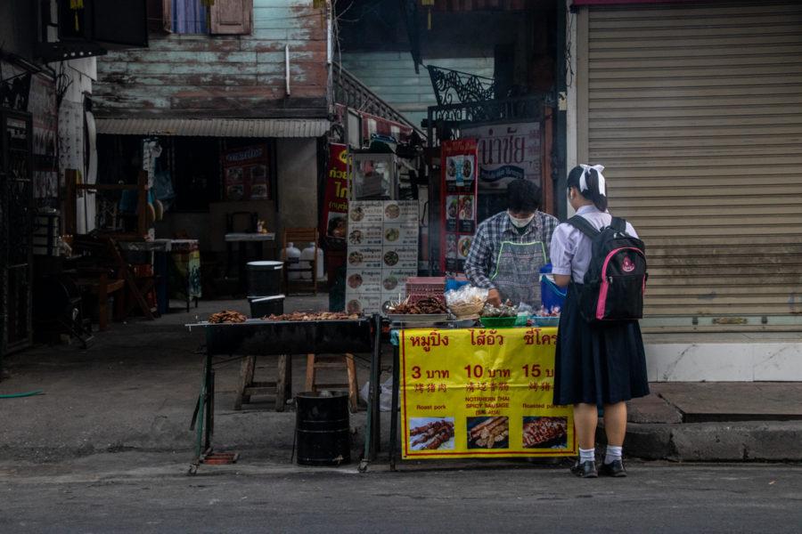 Auf dem Weg zur Schule besorgt sich dieses Mädchen ihr Frühstück an einem Streetfood-Stand.