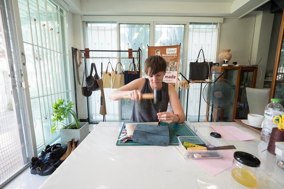 Mit dem Hammer und einem speziellen Werkzeug steche ich die Löcher vor, durch die ich später das Garn fädele. Foto: Suranat Leather Studio