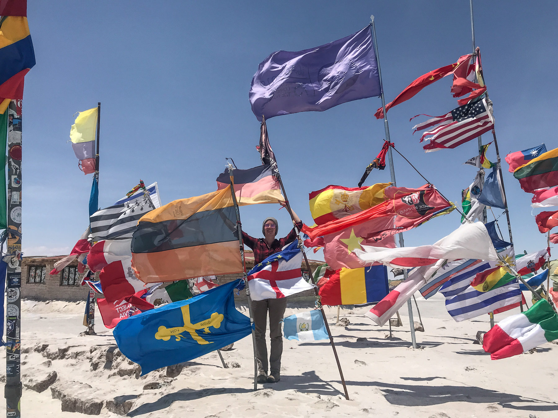 Between flags of all nations in the salt desert near Uyuni, Bolivia. Travel broadens the horizon.
